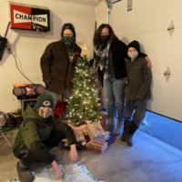 A photograph of a family celebrating Christmas in the garage.