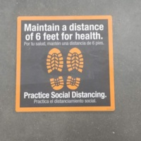 A sticker on the floor with foot prints asking to maintain six feet of distance.