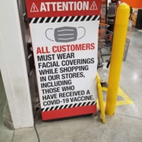 A sign saying that all customers must wear a mask including those who have been vaccinated
